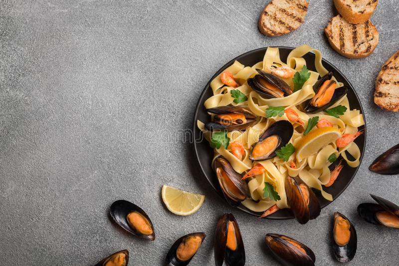 Tasty pasta with mussels, squid, parsley and lemon, top view royalty free stock photos
