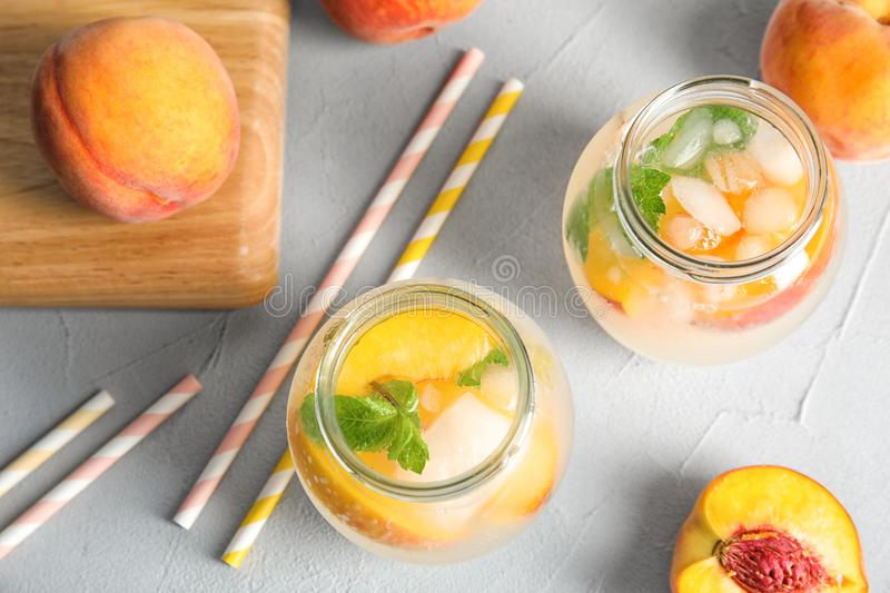 Tasty peach cocktail in glass jars on table. royalty free stock photography