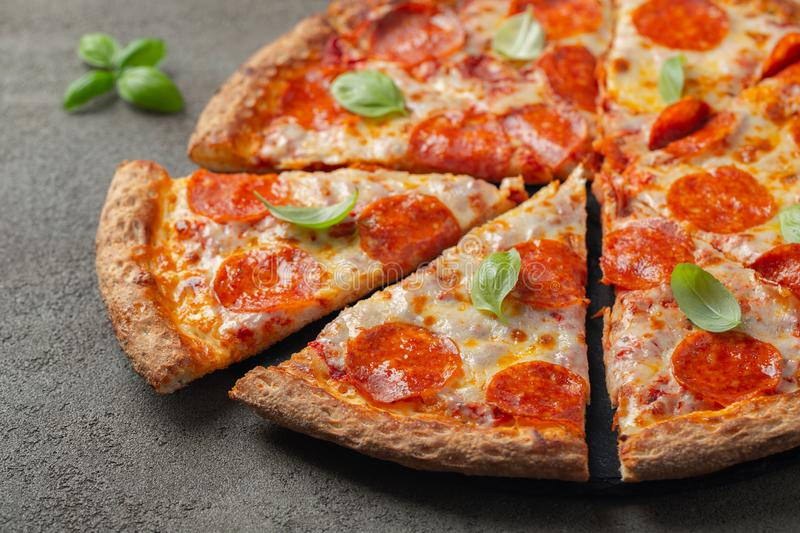 Tasty pepperoni pizza with basil on brown concrete background royalty free stock photo