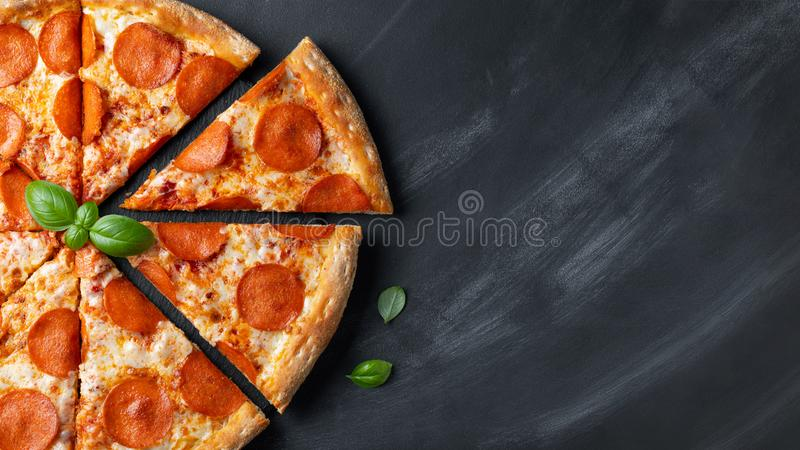 Tasty pepperoni pizza on black concrete background. Top view of hot pepperoni pizza. With copy space for text. Flat lay. Banner royalty free stock photo