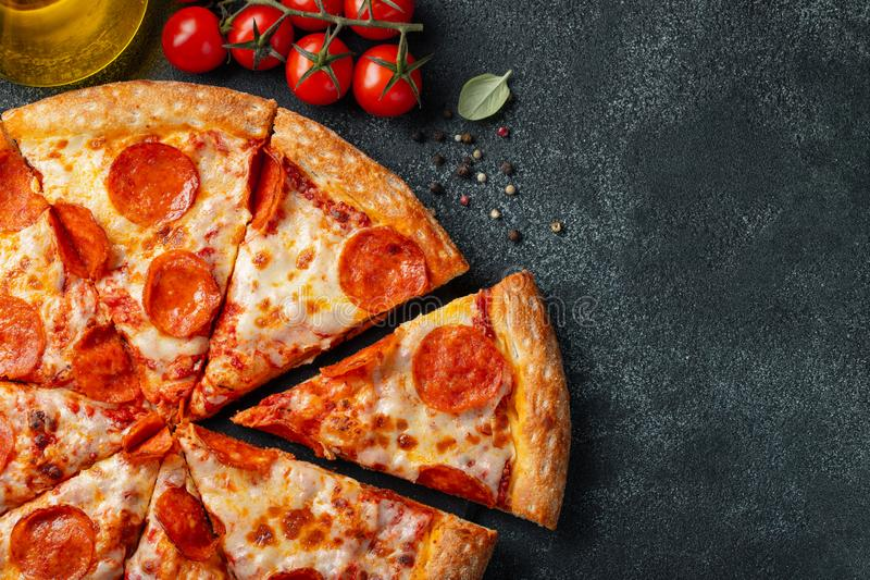 Tasty pepperoni pizza and cooking ingredients tomatoes basil on black concrete background. Top view of hot pepperoni pizza. With stock photos