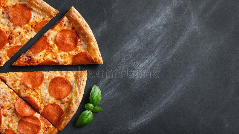 Tasty pepperoni pizza and cooking ingredients tomatoes basil on black concrete background. Top view of hot pepperoni pizza. With stock image