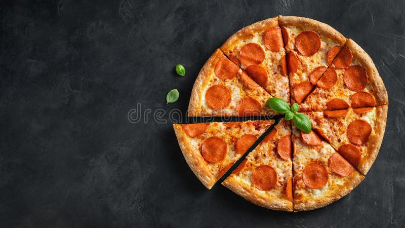 Tasty pepperoni pizza and cooking ingredients tomatoes basil on black concrete background. Top view of hot pepperoni pizza. With royalty free stock images