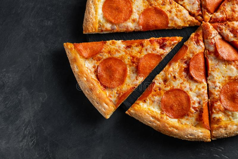 Tasty pepperoni pizza and cooking ingredients tomatoes basil on black concrete background. Top view of hot pepperoni pizza. Flat stock image