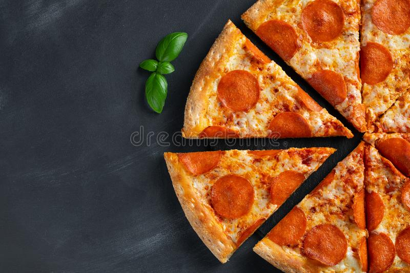 Tasty pepperoni pizza and cooking ingredients tomatoes basil on black concrete background. Top view of hot pepperoni pizza. With royalty free stock image