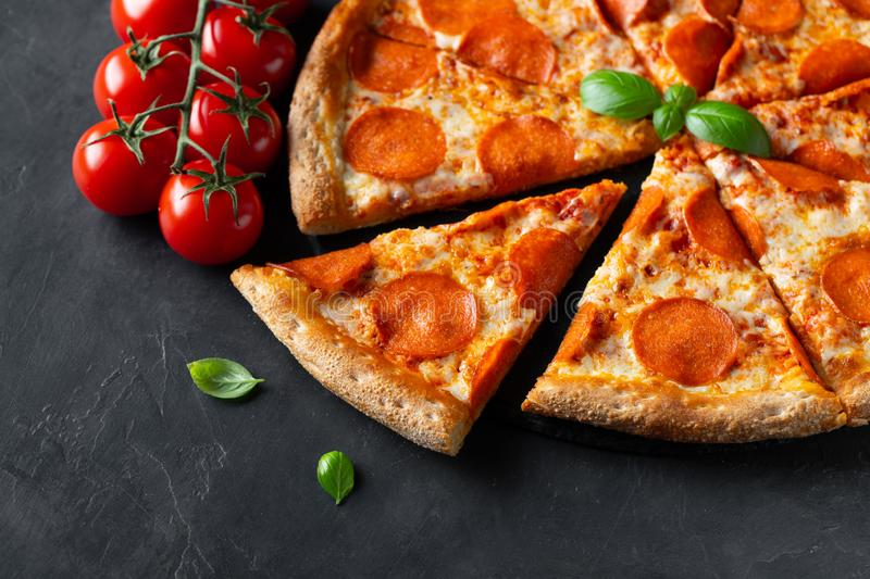 Tasty pepperoni pizza and cooking ingredients tomatoes basil on black concrete background. Top view of hot pepperoni pizza. Flat stock photos