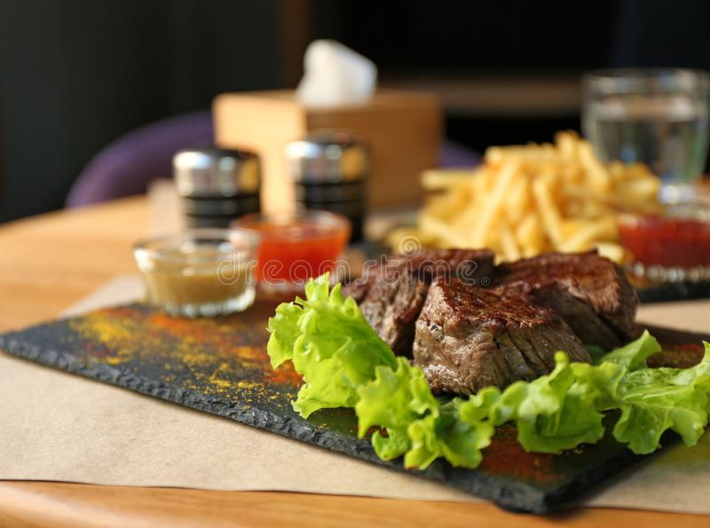 Tasty pieces of shish kebab served on slate plate. In cafe stock photography