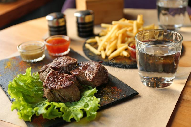 Tasty pieces of shish kebab served on slate plate. In cafe stock image