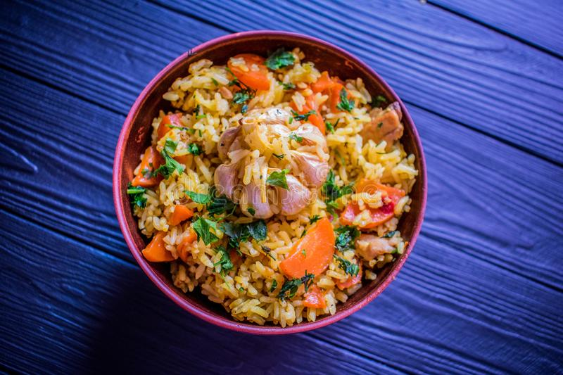 Tasty pilaf with meat on a purple wooden table stock photo