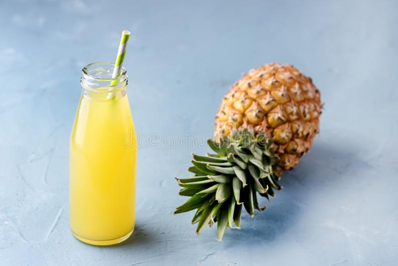 Tasty Pineapple Cocktail or Juice in Glass Bottle with Straw and Pineapple on a Blue Background royalty free stock photos