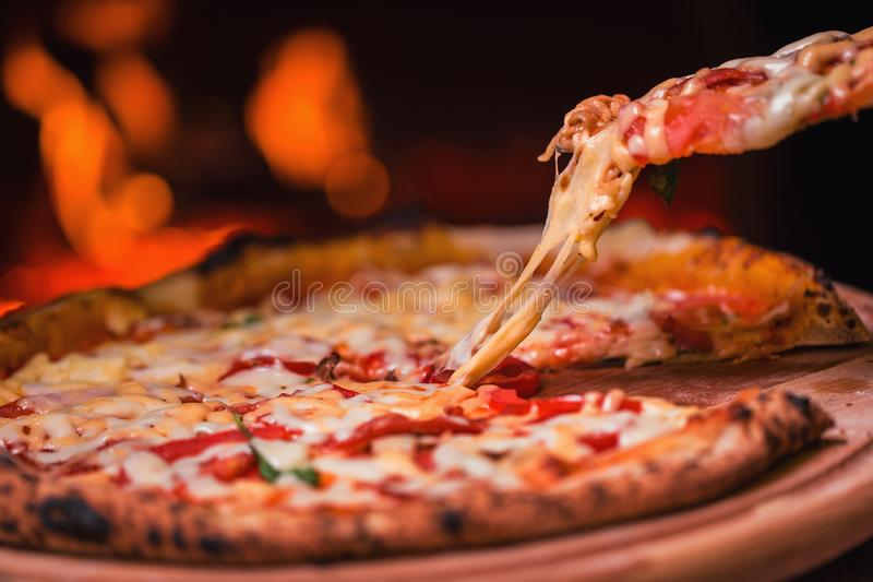 Tasty pizza out of oven in restaurant kitchen stock image