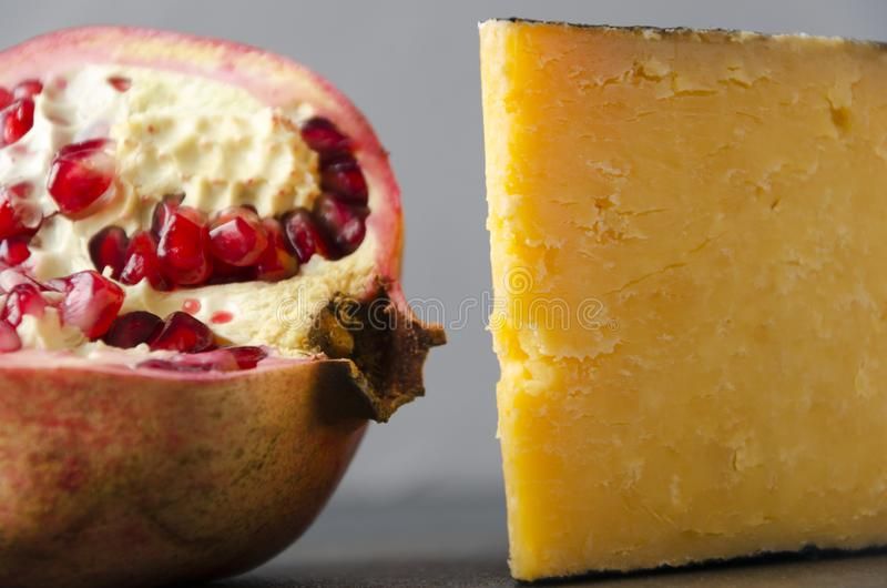 Tasty pomegranate and gouda cheese against grey wall.Closeup view.Fruits and dairy products stock photography
