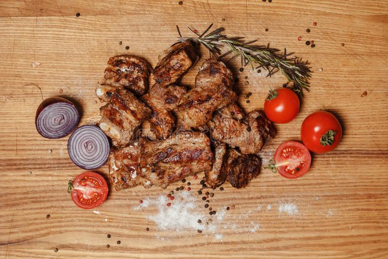 Tasty pork grilled meat. Juicy pork meat grilled. Close to the kebab lies fresh vegetables and onions stock photos