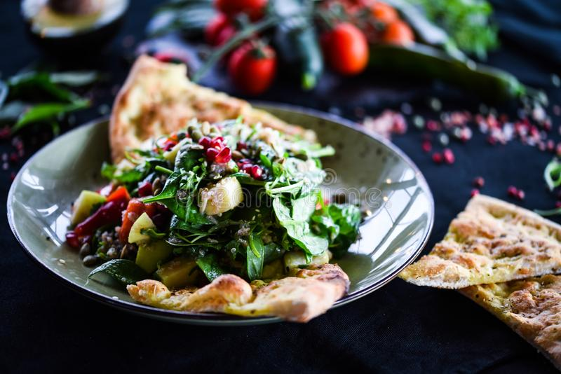 Tasty quinoa salad with fresh vegetables & focaccia bread royalty free stock photography