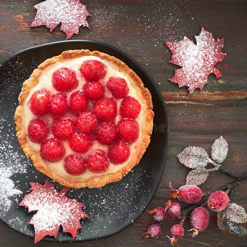 Tasty raspberry tart on a black ceramic plate, flat lay on dark. Tasty raspberry tart on a black ceramic plate, flat lay with frosted berries and marple leaf stock photo