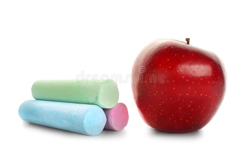Tasty red apple and three colorful crayons stock photos