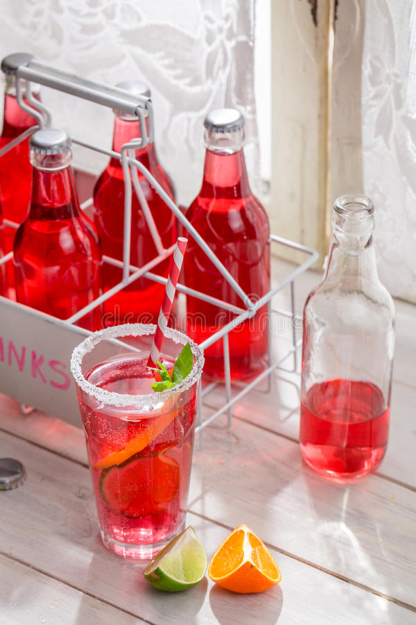 Tasty red orangeade in bottle with citrus fruit stock photography
