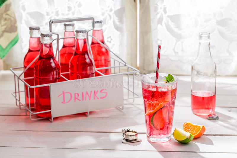 Tasty red summer drink in bottle with citrus fruit stock photos