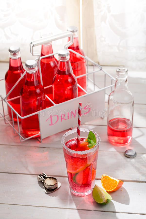 Tasty red summer drink in bottle with mint leaf stock image