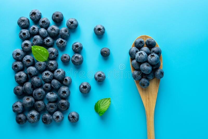 Tasty ripe blueberries on blue background with a spoon. Minimal food concept. Flat lay royalty free stock photos
