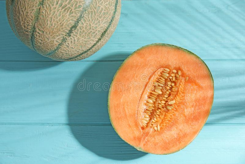 Tasty ripe cantaloupe melons and palm leaf shadow on light blue wooden table stock photo