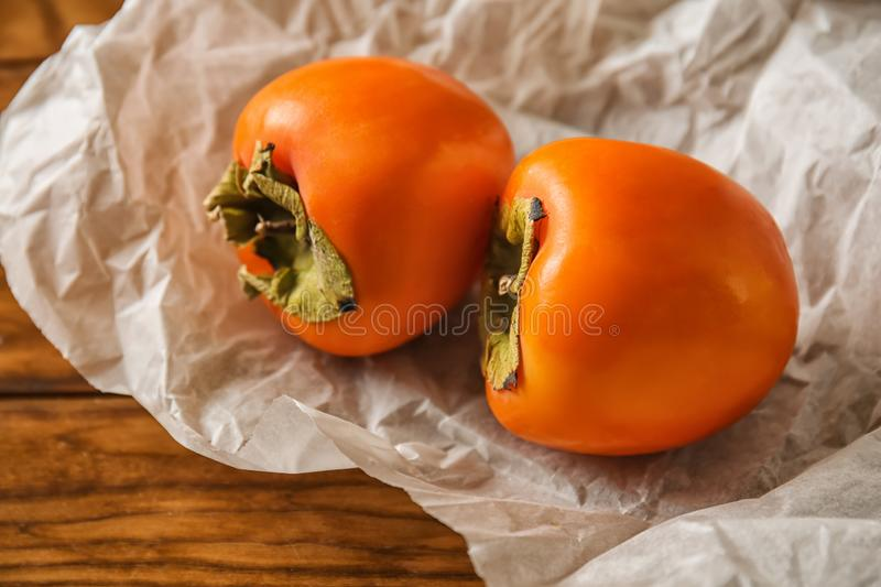 Tasty ripe persimmons on wooden table royalty free stock image
