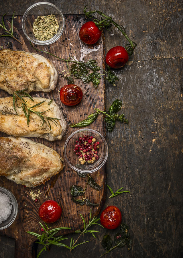 Tasty roasted chicken fillet with herbs,spices,seasoning and tomatoes on vintage gutting board over rustic wooden background, top stock image