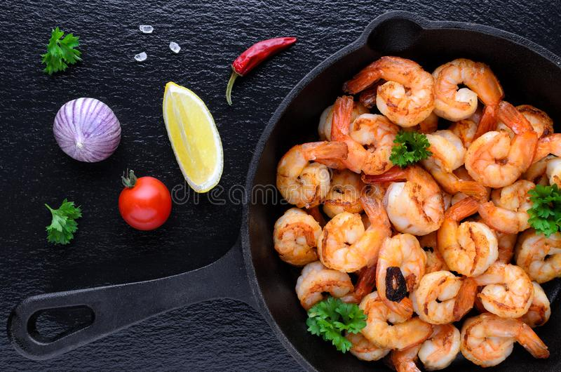 Tasty roasted shrimps in a cast iron pan with parsley and garlic, chili, tomato with lemon on black background royalty free stock photo