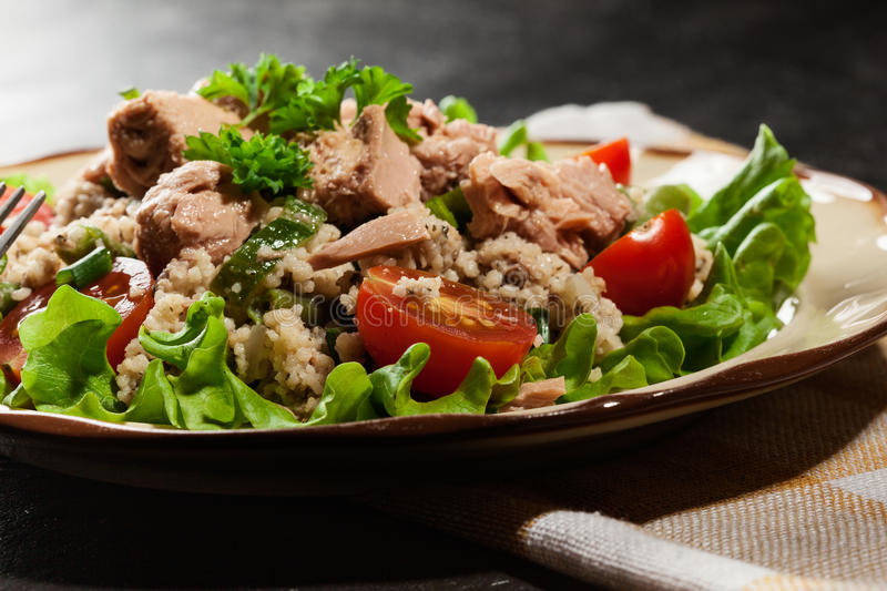 Tasty salad with couscous, tuna and vegetables royalty free stock image