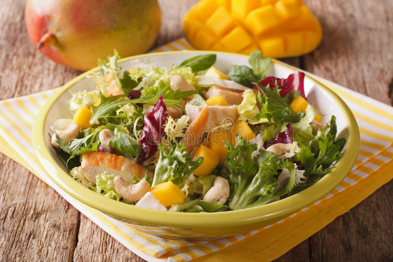 Tasty salad of grilled chicken breast, mango, arugula, lettuce a. Nd chicory close-up on the table. Horizontal stock photos