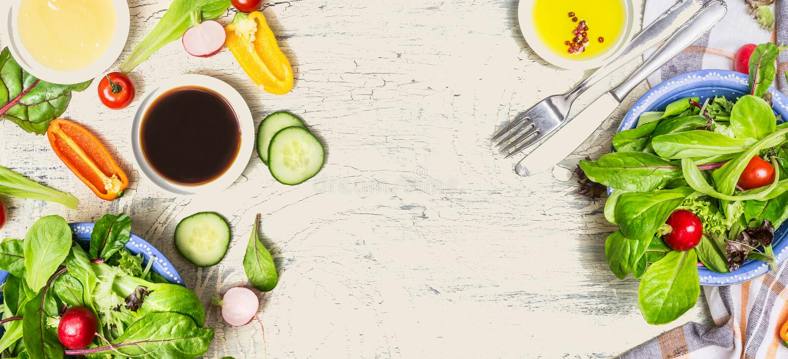 Tasty salad making with vegetables and dressing ingredients on light rustic background, top view, banner. Healthy lifestyle or detox diet food concept royalty free stock image