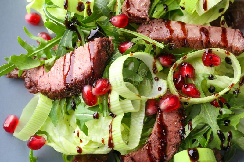 Tasty salad with meat and pomegranate seeds on plate, closeup royalty free stock images