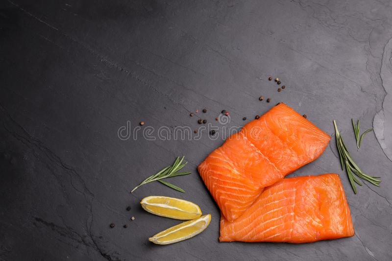 Tasty salmon fillet on black slate surface, flat lay. Space for text stock photography