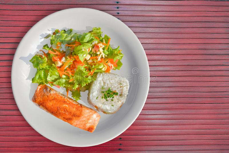 Tasty Salmon with rice and salad as a side royalty free stock image