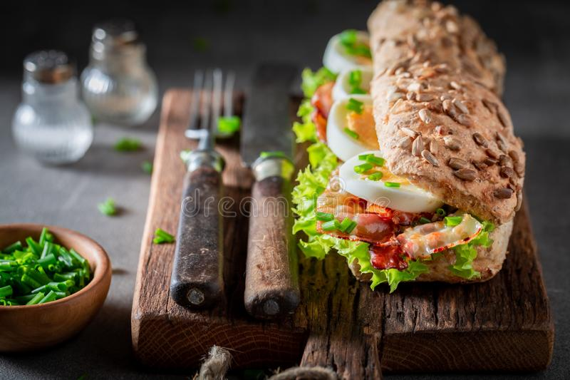 Tasty sandwich with bacon, chive and eggs. On wooden board stock photo