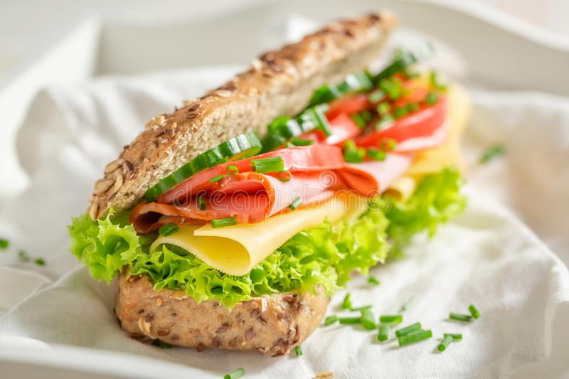 Tasty sandwich with cheese, ham and chive for breakfast. On white table stock image