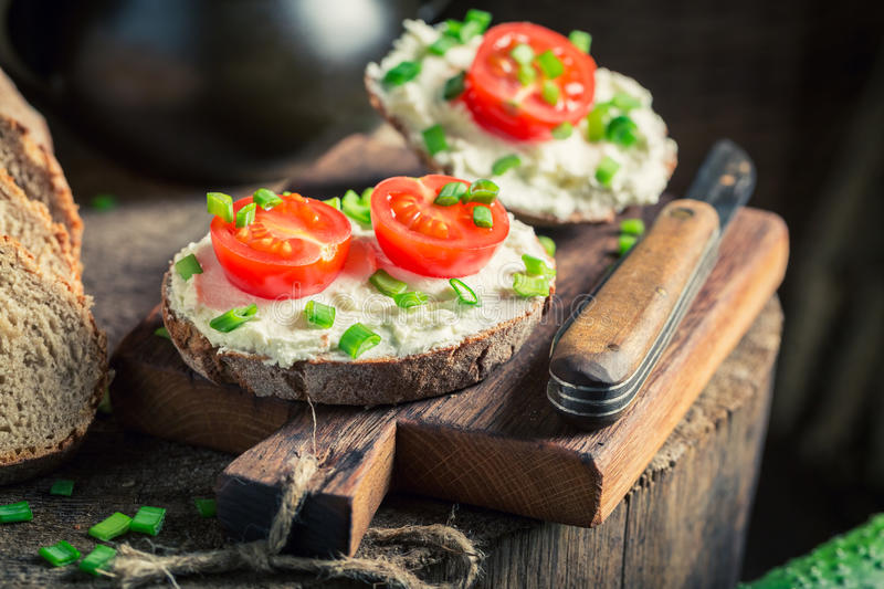 Tasty sandwich with fromage cheese, cherry tomatoes and chive. On wooden board stock photography