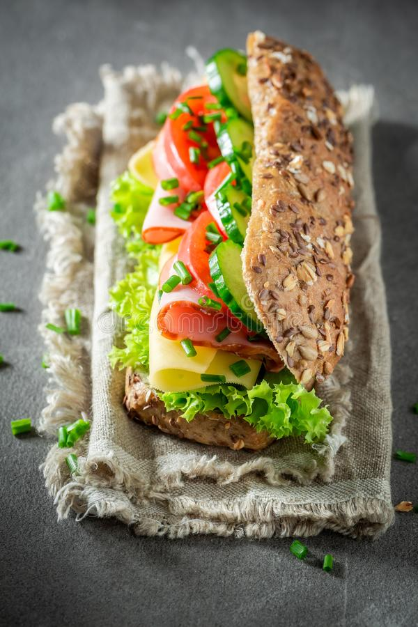Tasty sandwich with ham, lettue and chive for breakfast. On grey table royalty free stock photo