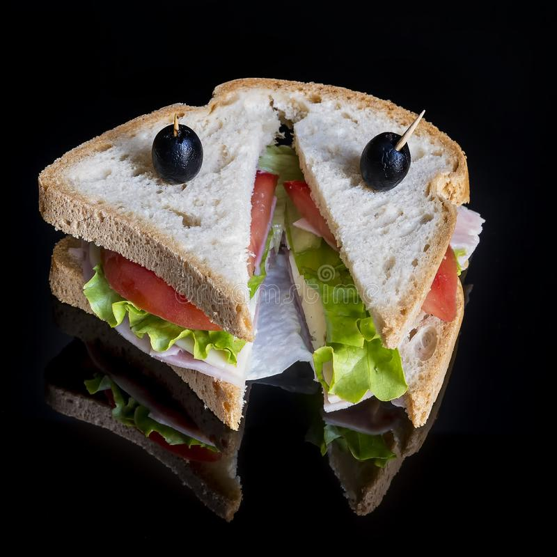 Tasty sandwich with salad, tomatoes, cheese and ham against shiny black background with reflection stock photo