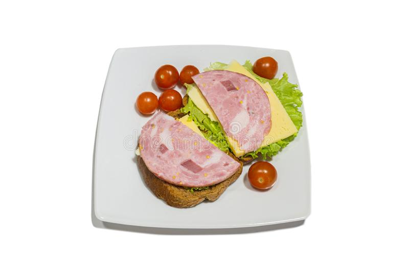 Tasty sandwich. slices of fresh bread with dried pork ham, green salad leaves and cherry tomatoes on white plate. isolated on royalty free stock photo