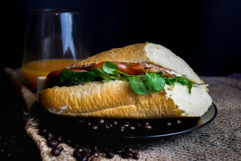 Tasty sandwich on table. A tasty sandwich on table with juice and coffee beans. the black background makes the whole picture mysterious. multiple uses can be royalty free stock photos