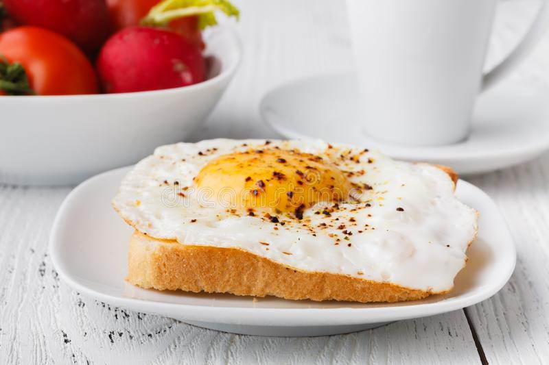 Tasty sandwich toast with avocado, tomato and poached egg on wooden chopping board royalty free stock photo