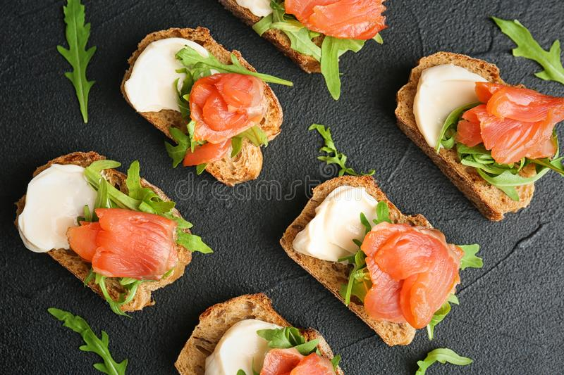 Tasty sandwiches with fresh sliced salmon fillet. On dark background, top view royalty free stock image