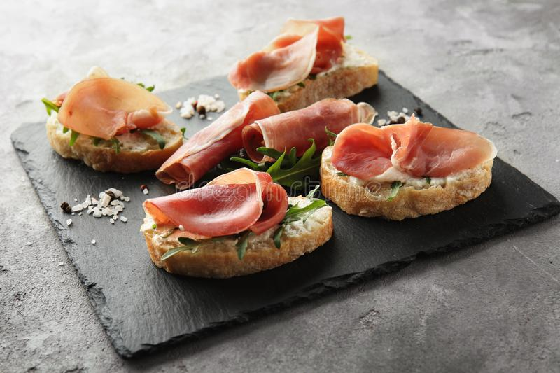 Tasty sandwiches with prosciutto slices on slate board royalty free stock image