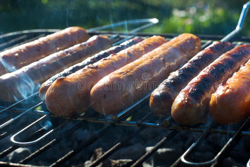 Spicy sausages grilling on portable barbecue on summer picnic. Outdoors. Smoke and fire. Close up. Tasty sausages grilling on portable barbecue on summer picnic royalty free stock images