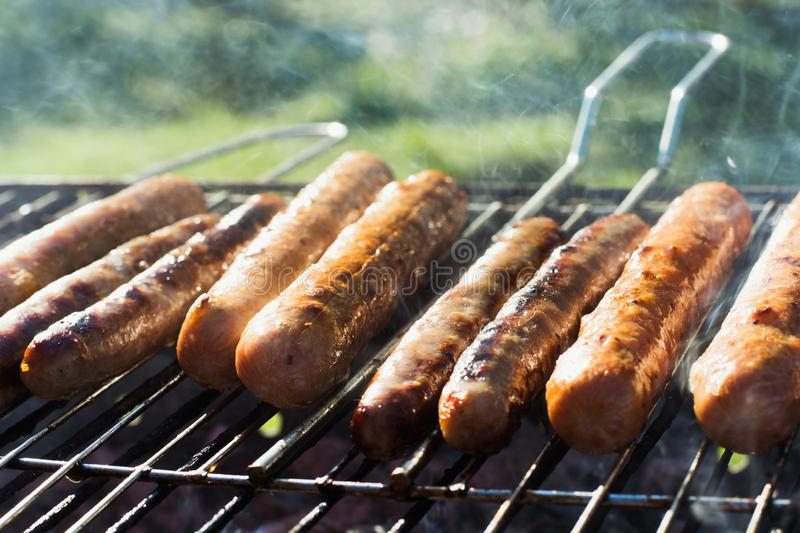 Spicy sausages grilling on portable barbecue on summer picnic. Outdoors. Smoke and fire. Close up. Tasty sausages grilling on portable barbecue on summer picnic royalty free stock photo