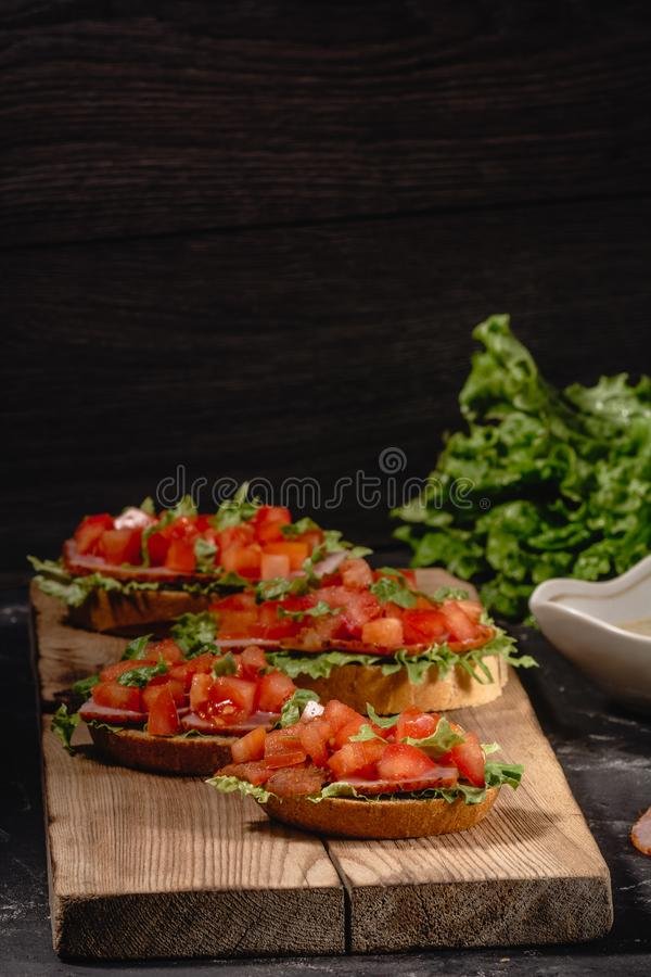 Tasty savory tomato Italian appetizers, or bruschetta, on slices of toasted baguette garnished with salad leaves, ham, chopped stock photo