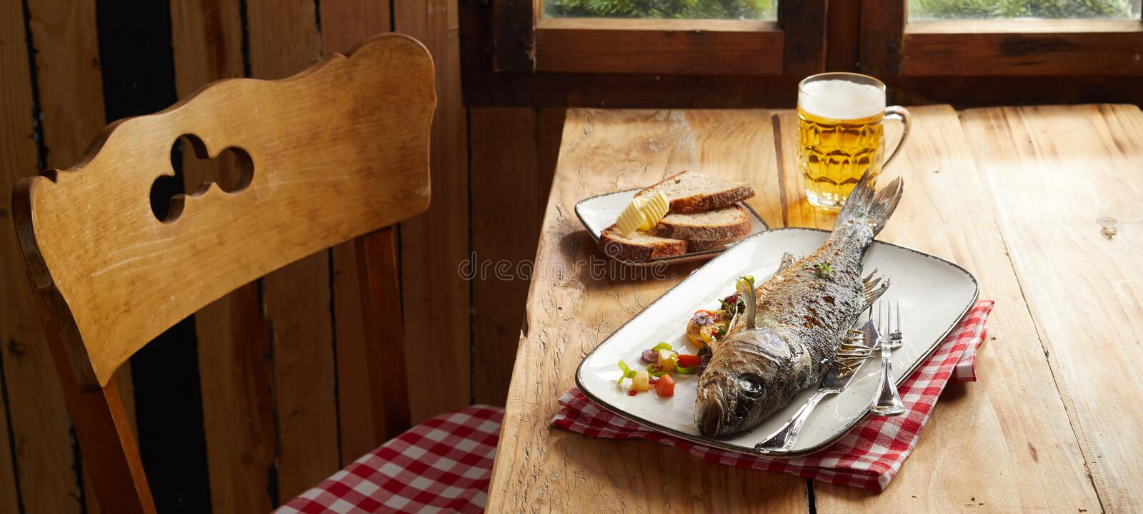 Tasty seafood pub lunch with oven roasted sea bass. Seasoned with fresh herbs and served with a mug of cold beer at a rustic table stock image