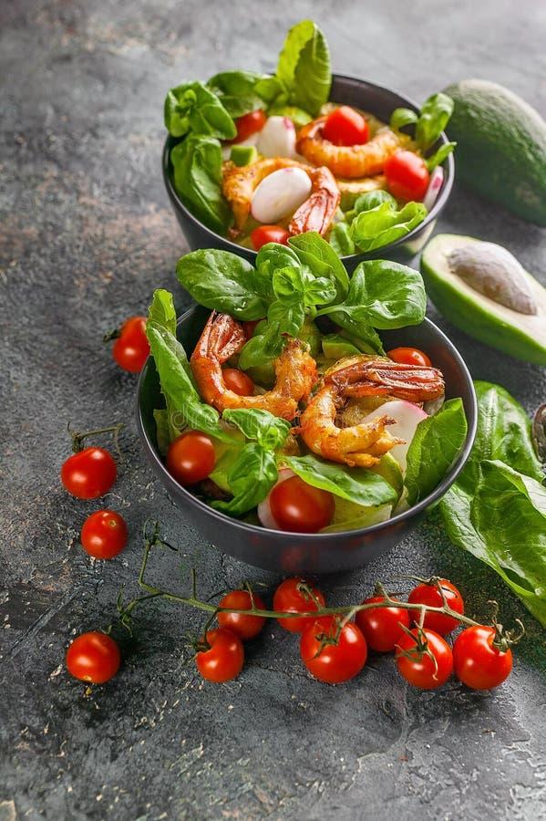Tasty seafood salad. Shrimp, avocado, lettuce in a bowl on a dark background. Vertical shot stock photo