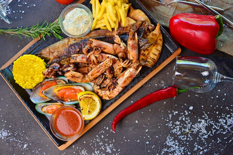 Tasty grilled seafood with French fries on a table of a restaurant cuisine. Tasty seafood on a table of a restaurant cuisine. Mediterranean cuisine royalty free stock photography